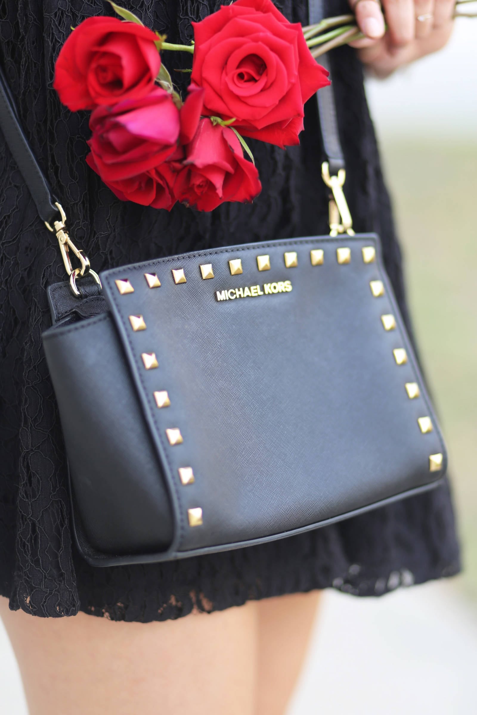Fashion blogger Mash Elle styles the MICHAEL Michael Kors Black Medium Selma Studded Messenger Bag with a black lace dress